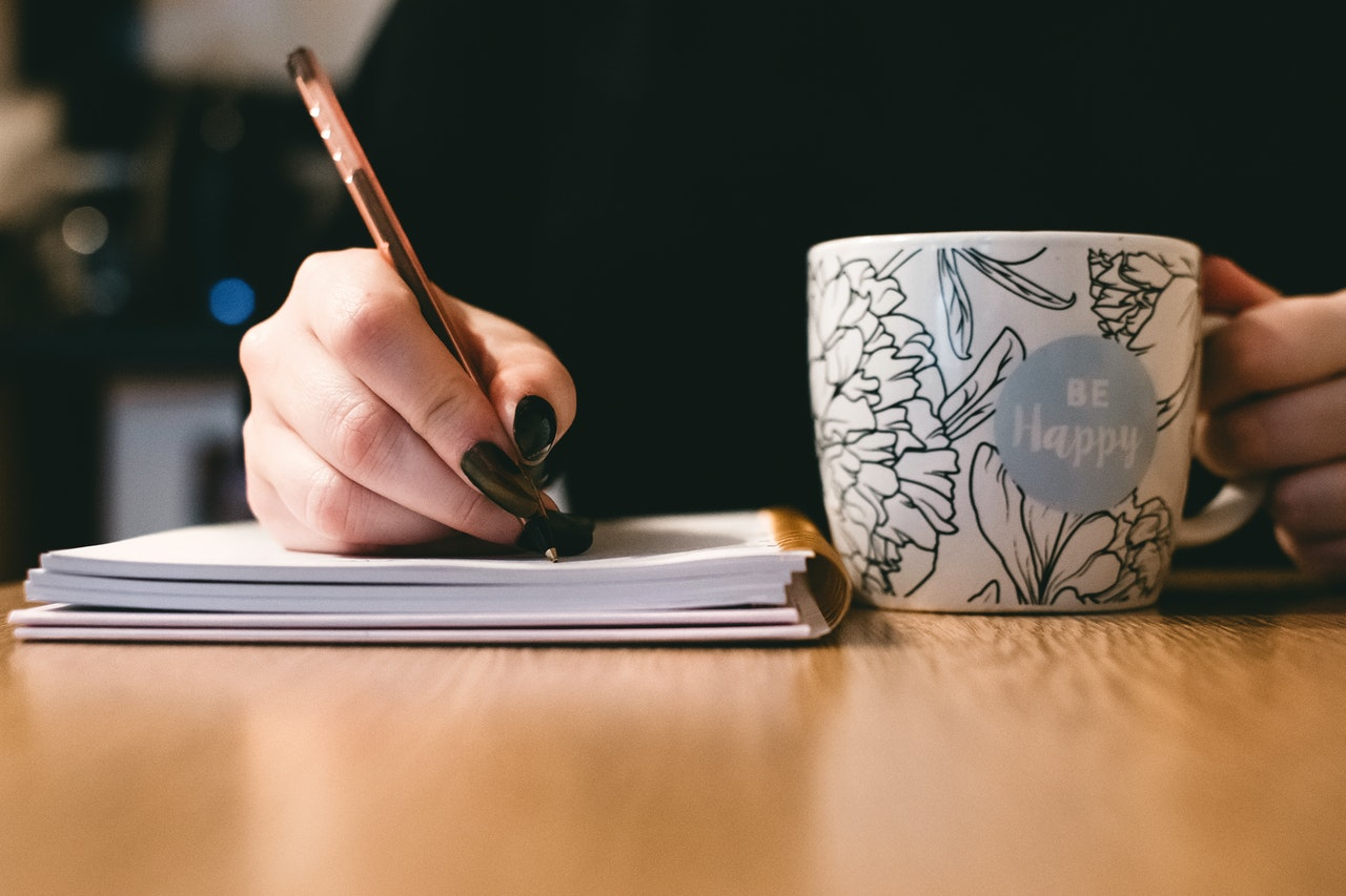 woman writing down topics for book